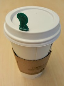 Hot_Stopper_in_the_lid_of_a_paper_coffee_cup_with_a_cardboard_sleeve