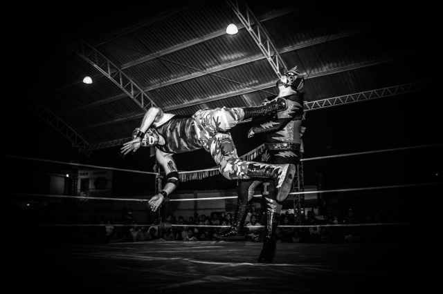 grayscale photography of wrestler on field